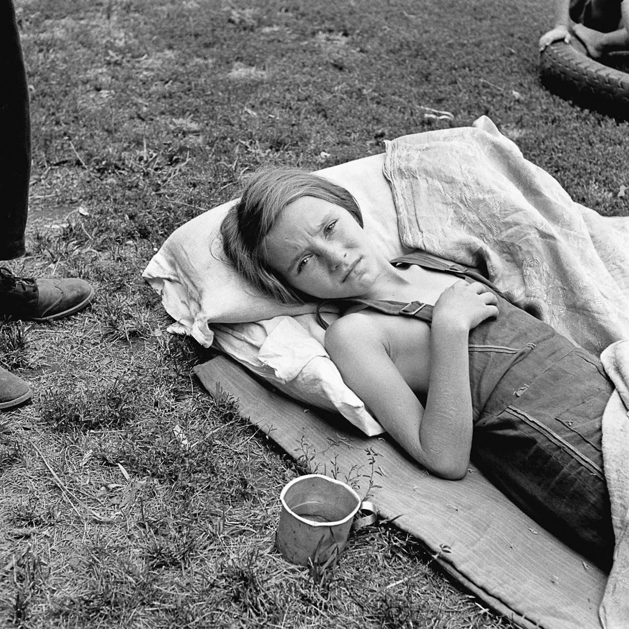 Dorothea Lange, <em>MIGRANT GIRL, 1930'S. /nA sick migrant girl resting on a makeshift bed outside, Yakima Valley, Toppenish, Washington.</em>